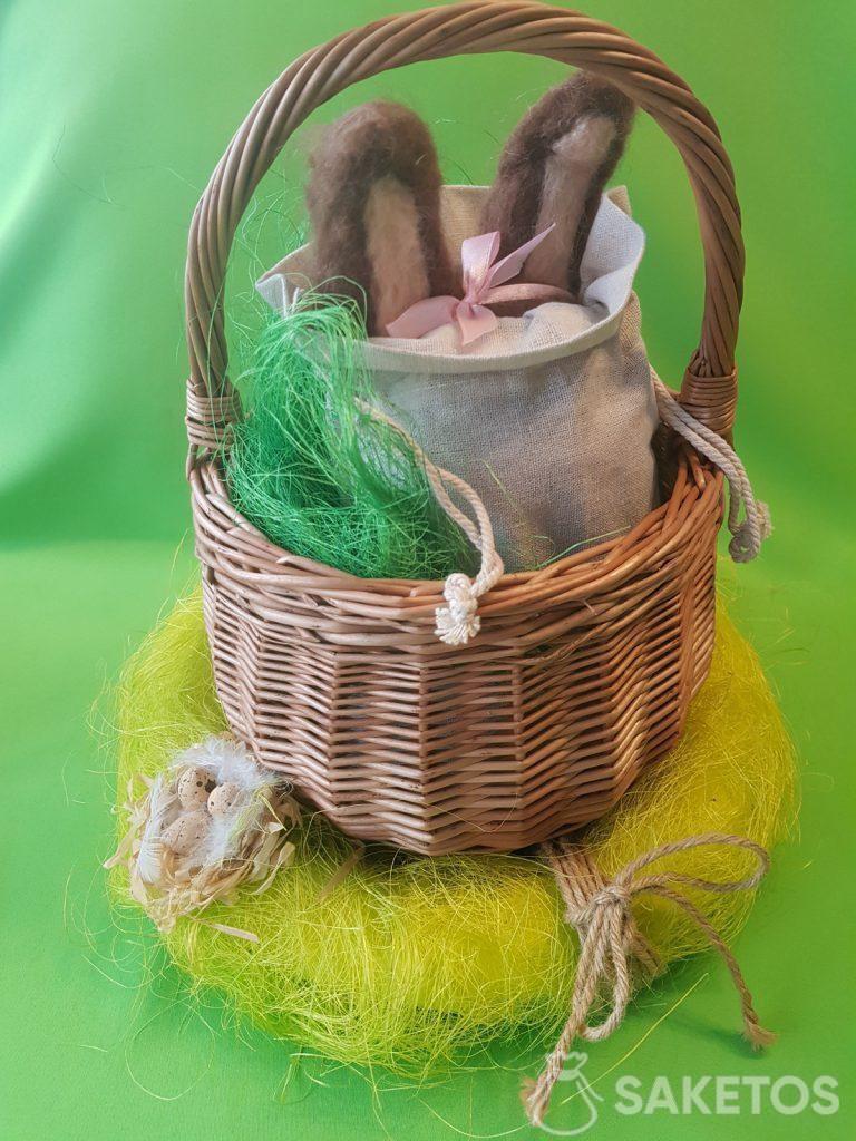 Cesta con una bolsa de lino de la que sobresalen las orejas de un conejo de lana peinada.