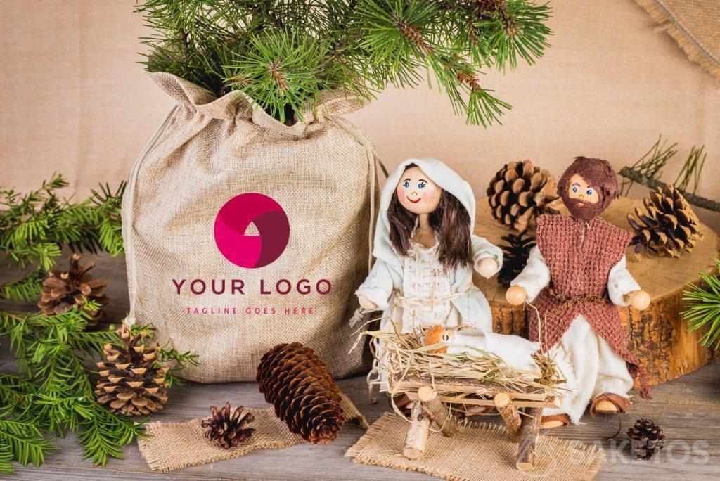 Un belén navideño y un jarrón con una rama de coníferas colocada en una bolsa de arpillera