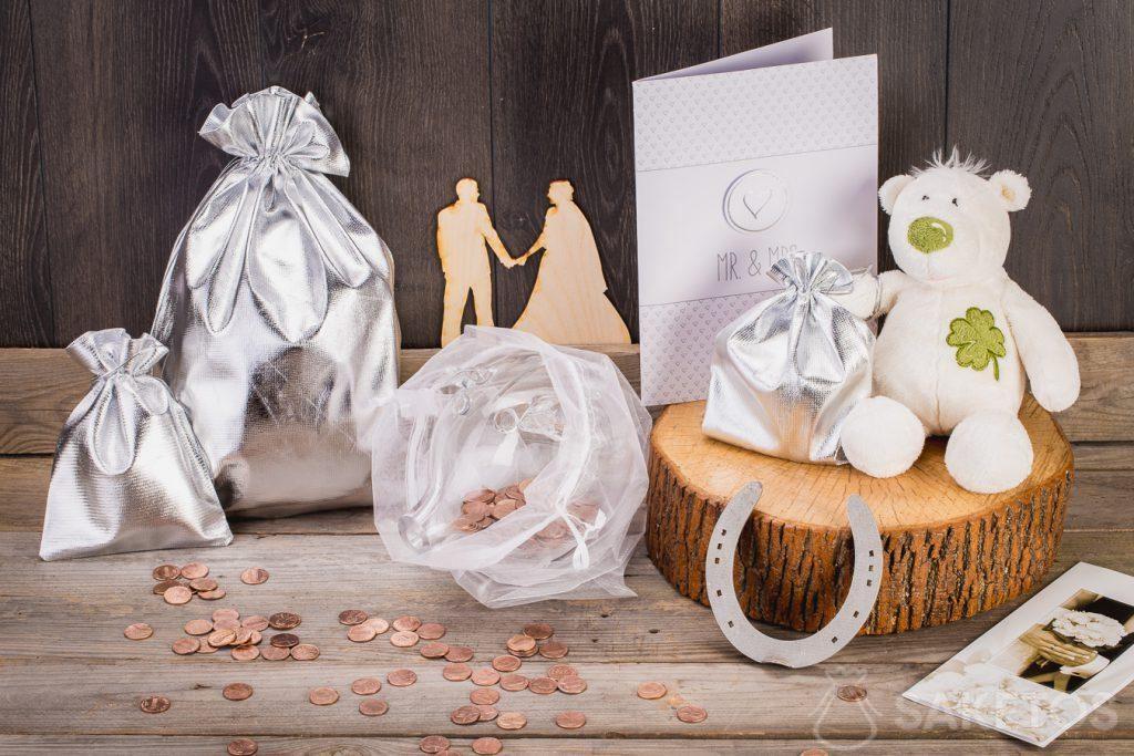 Cuando un regalo de boda se supone que es dinero, usted puede empaquetarlo en una alcancía de vidrio colocada en una bolsa de organza.