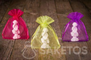 Figuras de ángeles empaquetadas en una bolsa de organza de color para agradecer a los invitados de la boda