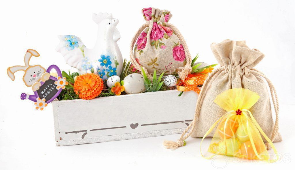 Una colorida composición de Pascua creada de bolsas de tela y una maceta rectangular con huevos de Pascua