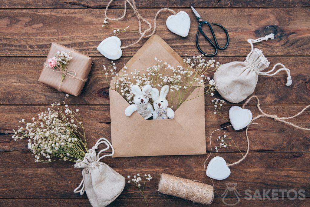 Una bolsa de lino de yeso, conejos en un sobre y un regalo envuelto en papel gris.