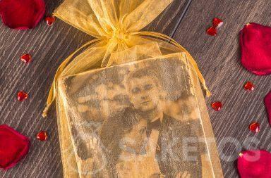 Elegante y dorada bolsa de organza que sirve de envoltorio para la foto de los recién casados