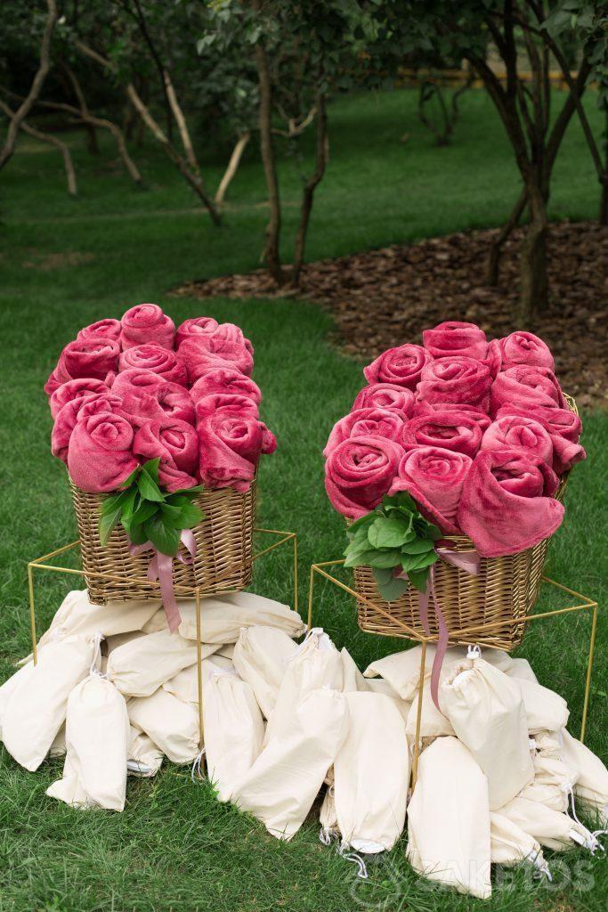 Mantas decorativas enrolladas y pantuflas en bolsas de lino preparadas para los invitados de la boda.