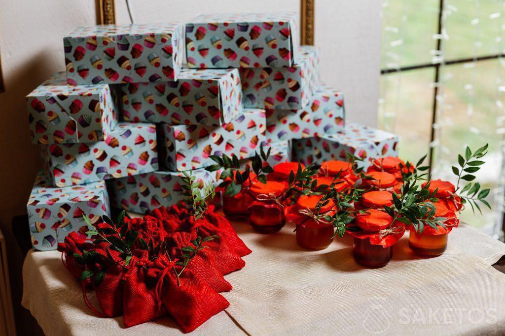 Cajas de regalo envueltas en papel de colores, bolsas rojas de yute y tarros con conservas