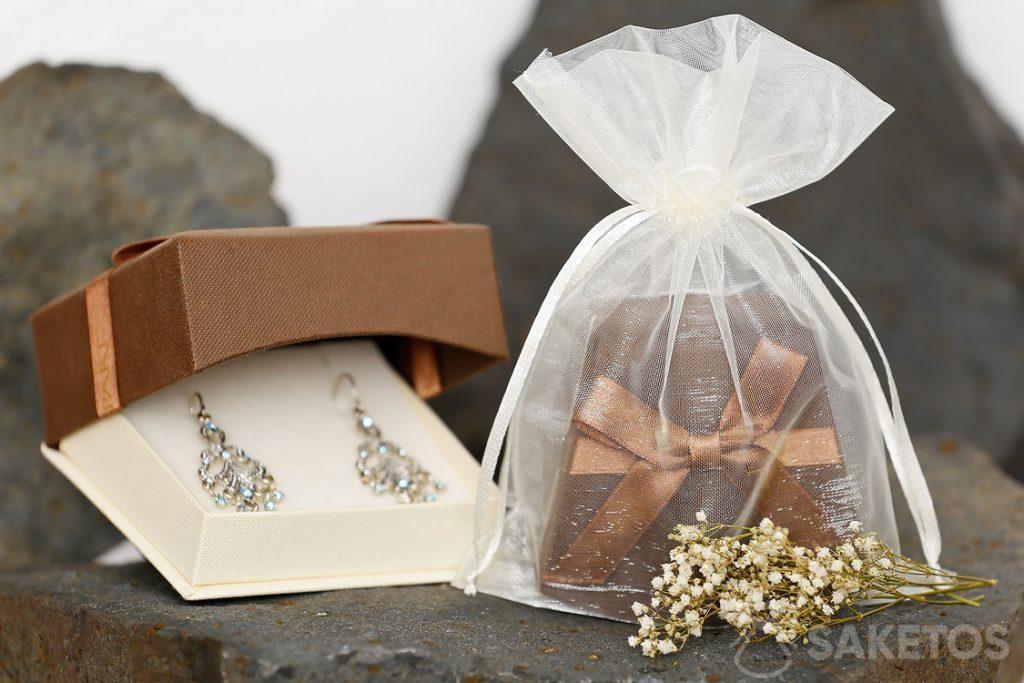Una caja de regalo con joyas empacadas en una bolsa de organza se ve muy elegante.
