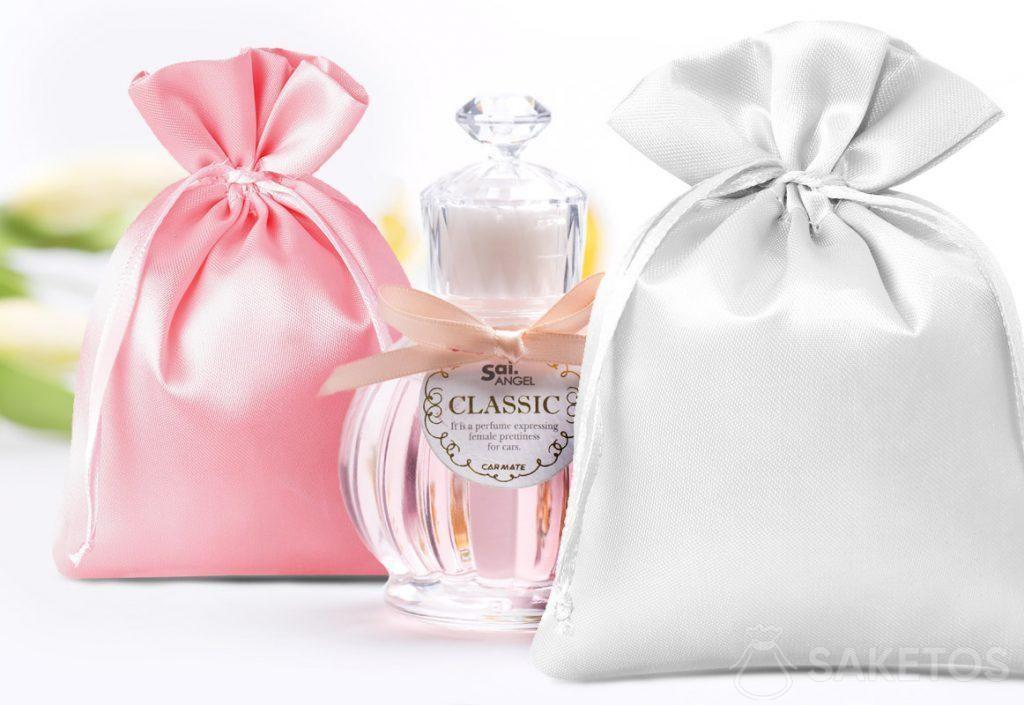 Bolsas de satén en rosa y plateado y un frasco de perfume decorativo