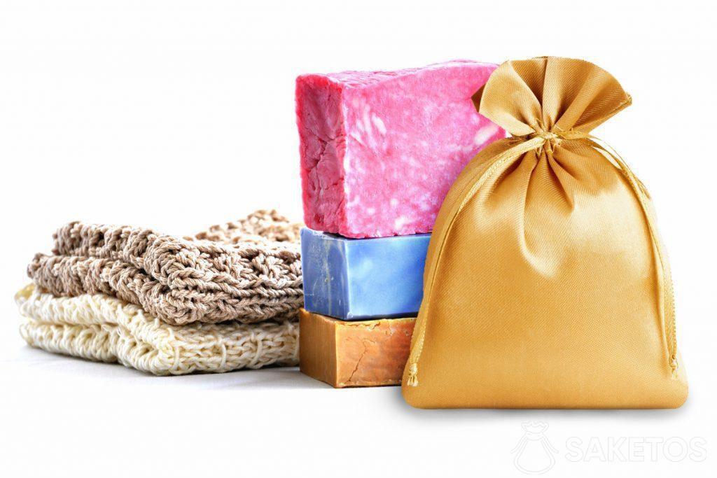 Jabones de colores y una bolsa de satén dorada.
