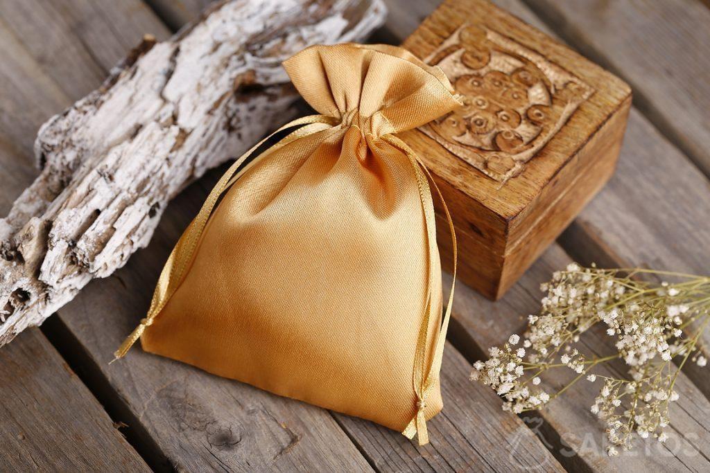 Bolsa de satén dorada y un pequeño cofre de madera para recuerdos
