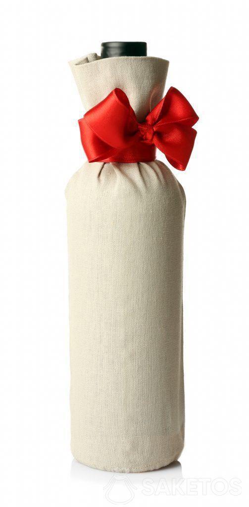 Una botella de alcohol empacada como regalo en una bolsa de lino con un lazo rojo.