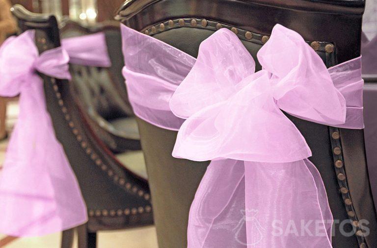 Lazo de organza decorativo atado en el respaldo de una silla