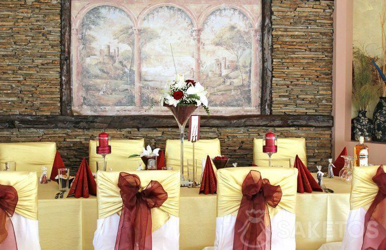 Decoración de mesa en color burdeos: un jarrón, servilletas, candelabros y lazos en las sillas
