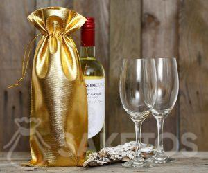 Una botella de vino envuelta en una bolsa metálica dorada.