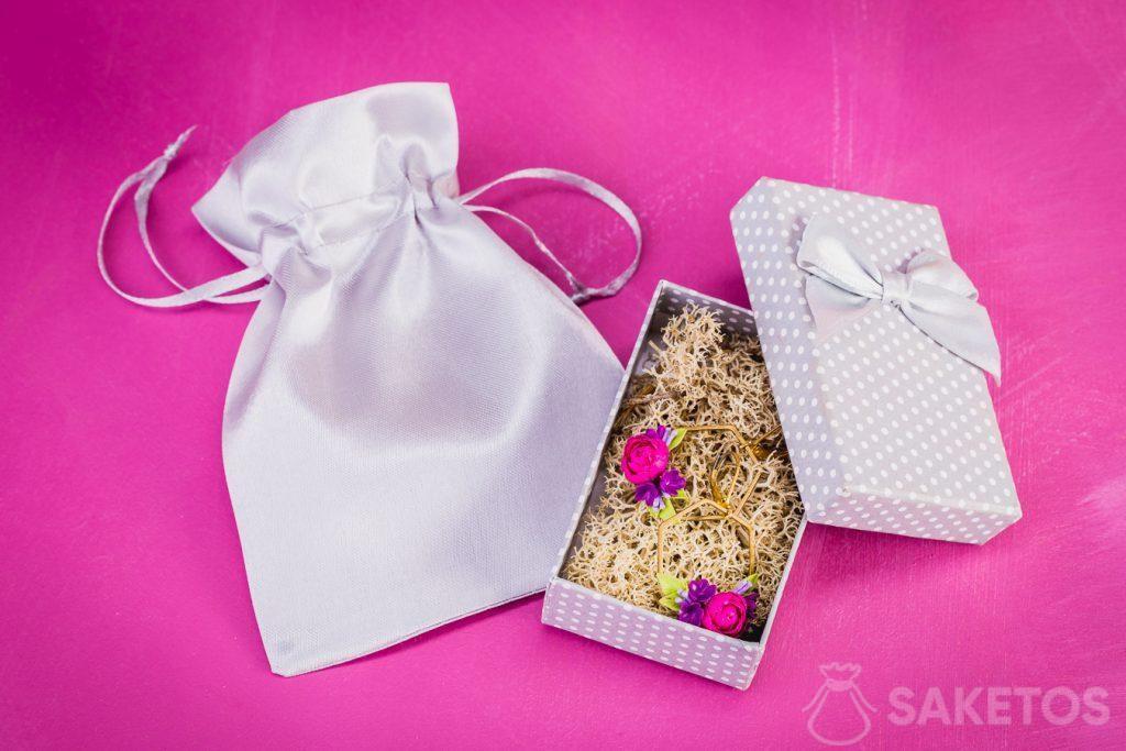 Pendientes envueltos para regalo en un joyero y una bolsa de satén